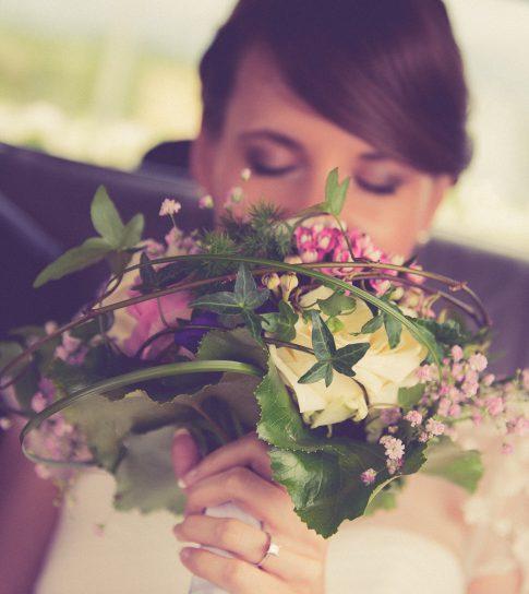 Brautstrauß und Braut im Hochzeitsauto