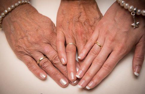 Drei Hände mit Eheringen