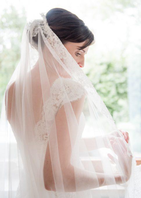 Braut mit Schleier am Fenster